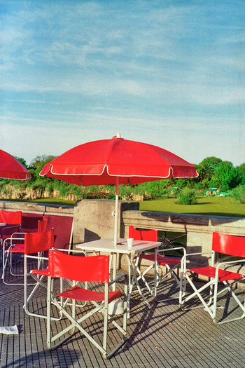 Empty chairs and tables in cafe against sky