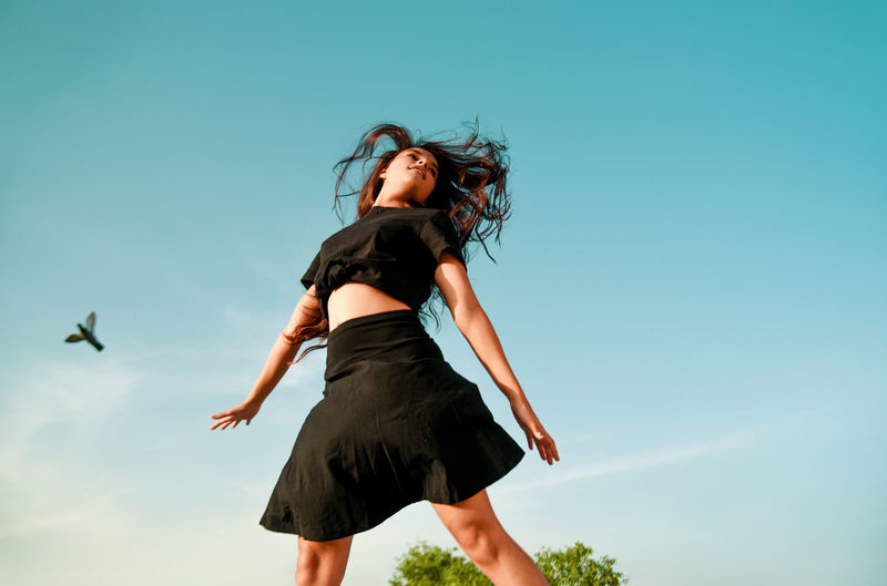 Low angle view of young woman dancing against blue sky