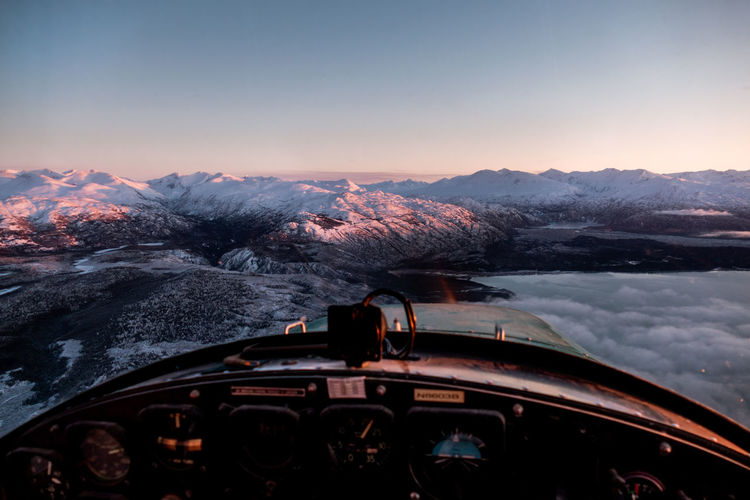 Scenic view of snow covered landscape seen through helicopter window against sky