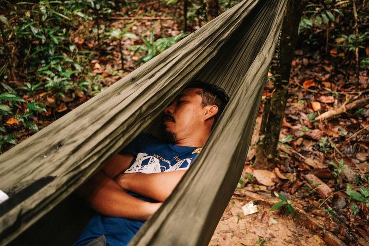 Portrait of man relaxing on hammock in forest