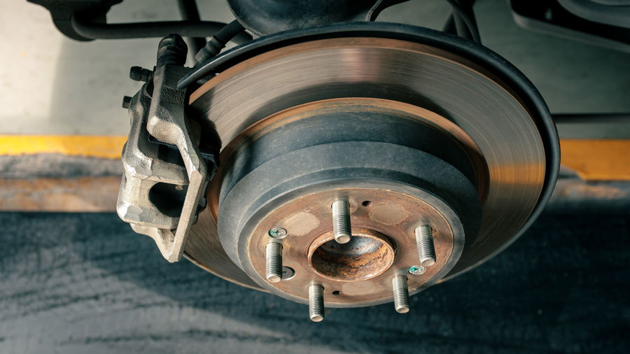 Car disc brake to be fixed at garage or automotive service station, process of tire replacement