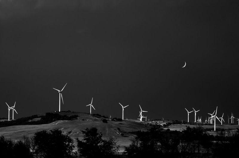 Wind turbines on land against sky at night