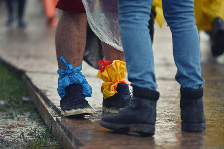 Low section of man tied polythene bag on leg while standing on street