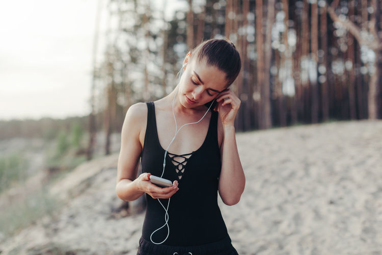 Woman listening music while standing at beach