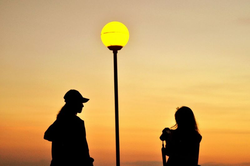 Silhouette women standing by street light against orange sky