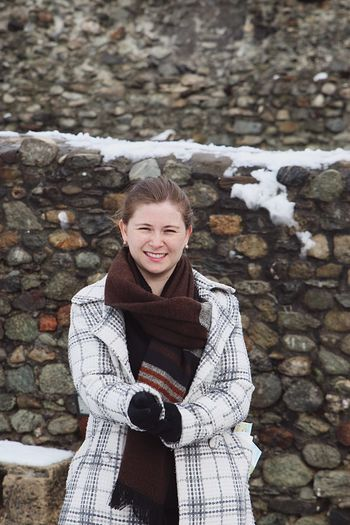 Portrait of smiling woman standing against stone wall