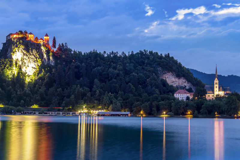 The Bled Castle lighted during the blue hour overlooking the lake on a summer day. Slovenian castle on a cliff illuminated at night with water reflections Bled Castle Church Lights Rock Slovenia The Traveler - 2018 EyeEm Awards Blue Cliff Defense Forest Fortification Fortress Historic Illuminated Lake Medieval Night Old Outdoors Reflections Sky Traditional Village Water