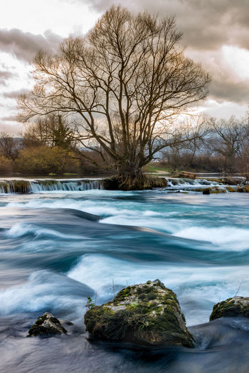 Scenic view of river stream against sky during winter