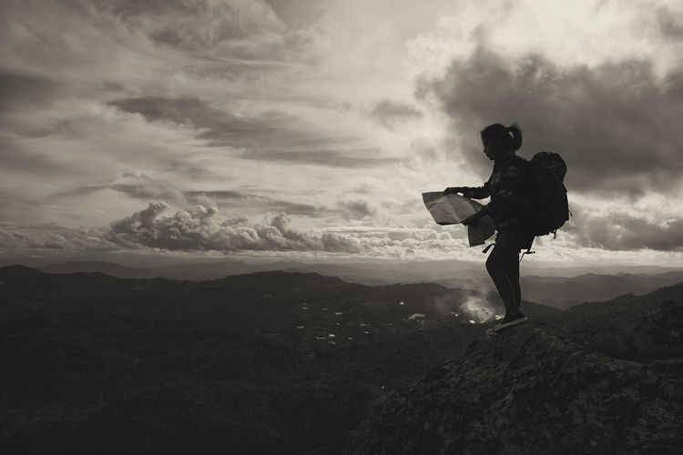 Female Hiker Looking In Map While Standing On Mountain Against Cloudy Sky
