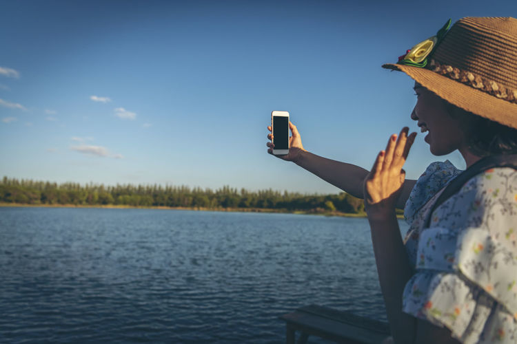 Man photographing with mobile phone against sky