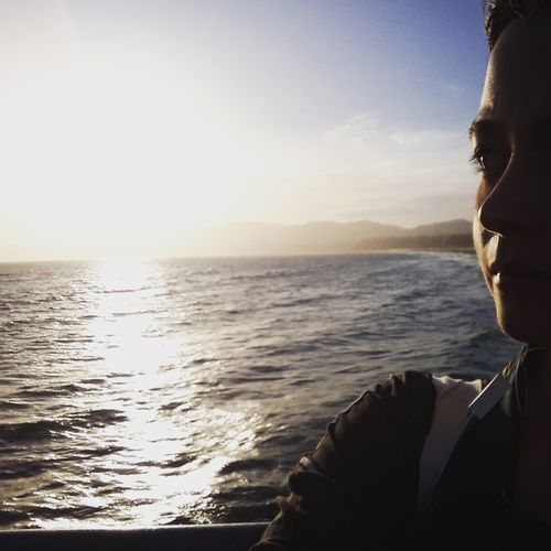 Woman Looking Away At Sea Against Sky