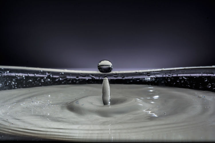 Close-up of drop falling on water against black background