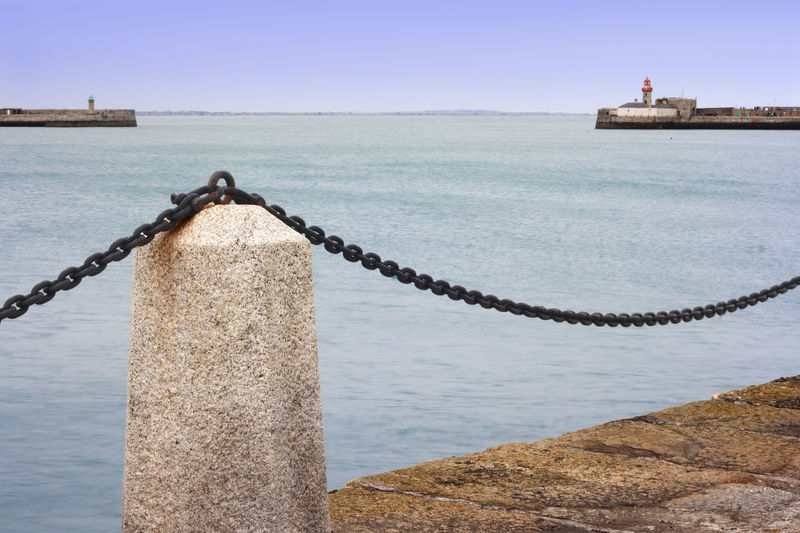 Marine landscape at promenade of port Water Sea No People Day Architecture Sky Nature Chain Rope Post Built Structure Outdoors Harbor Bollard Focus On Foreground Metal Strength Nautical Vessel Wooden Post