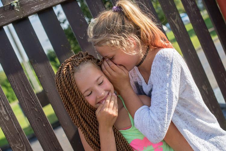 Tilt image of girl whispering to female friend by fence