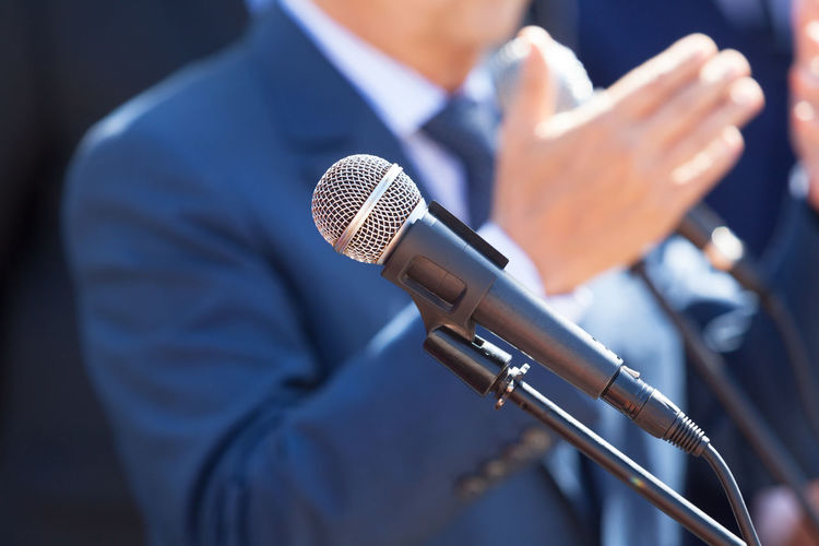 News conference. Microphone in focus against blurred speaker. Event PR Press Broadcast Broadcasting Journalism Communication Human Hand Information Journalism Media Media Event Media Interview Microphone News News Conference News Event Presentation Press Conference Public Relations Speaker Unrecognizable Person