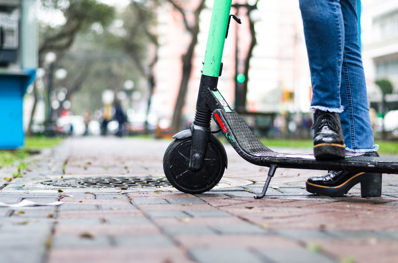 Low section of woman with segway standing on footpath
