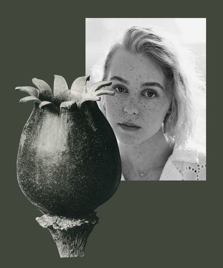 Portrait of woman holding flower against black background
