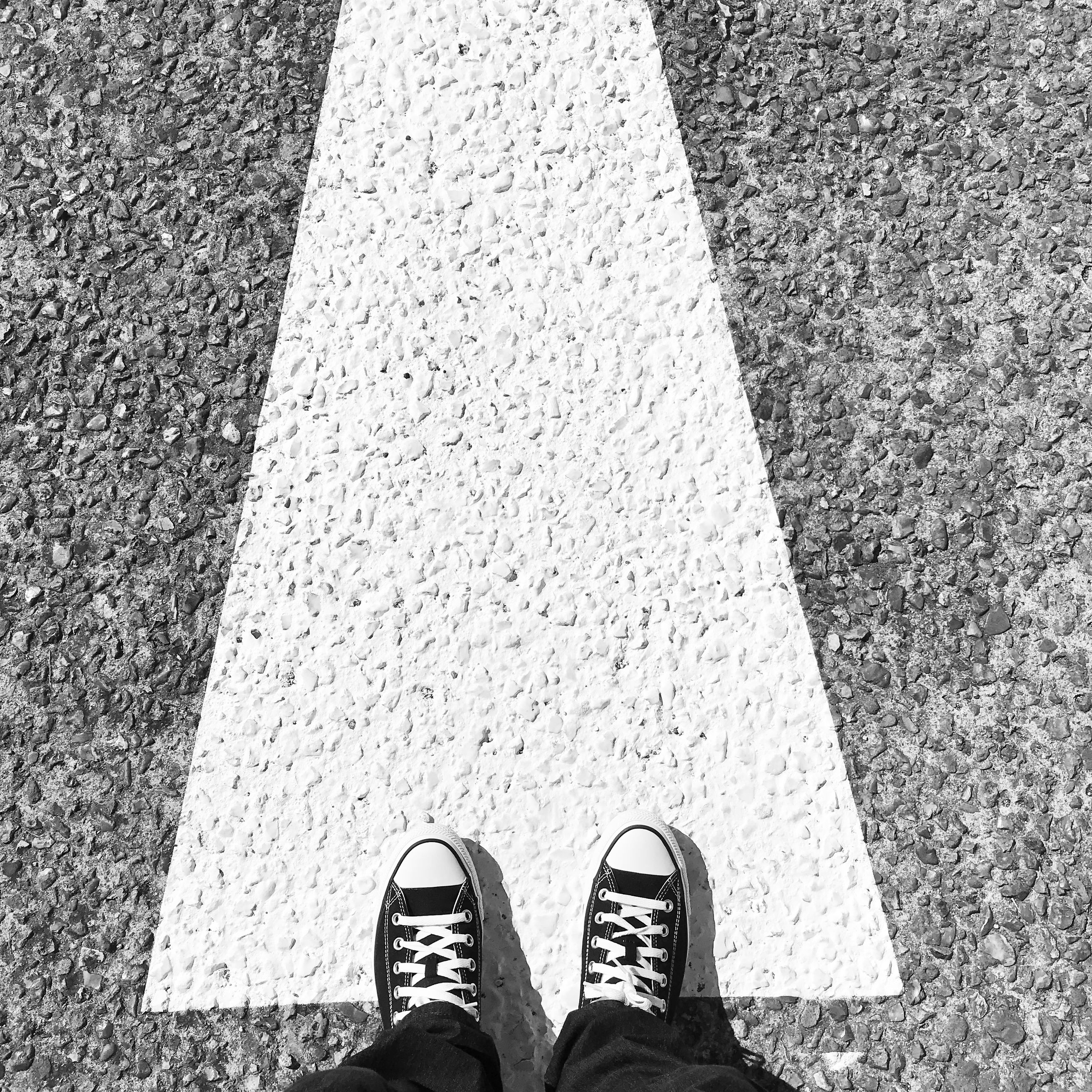 low section, human leg, one person, shoe, standing, high angle view, personal perspective, road, black, day, sign, symbol, transportation, street, city, lifestyles, asphalt, white, road marking, marking, human foot, men, black and white, human limb, limb, road surface, footwear, directly above, leisure activity, outdoors, lane, monochrome, communication, guidance, monochrome photography