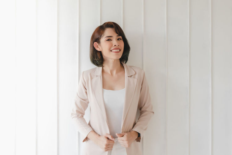 Portrait of a smiling young woman standing against wall