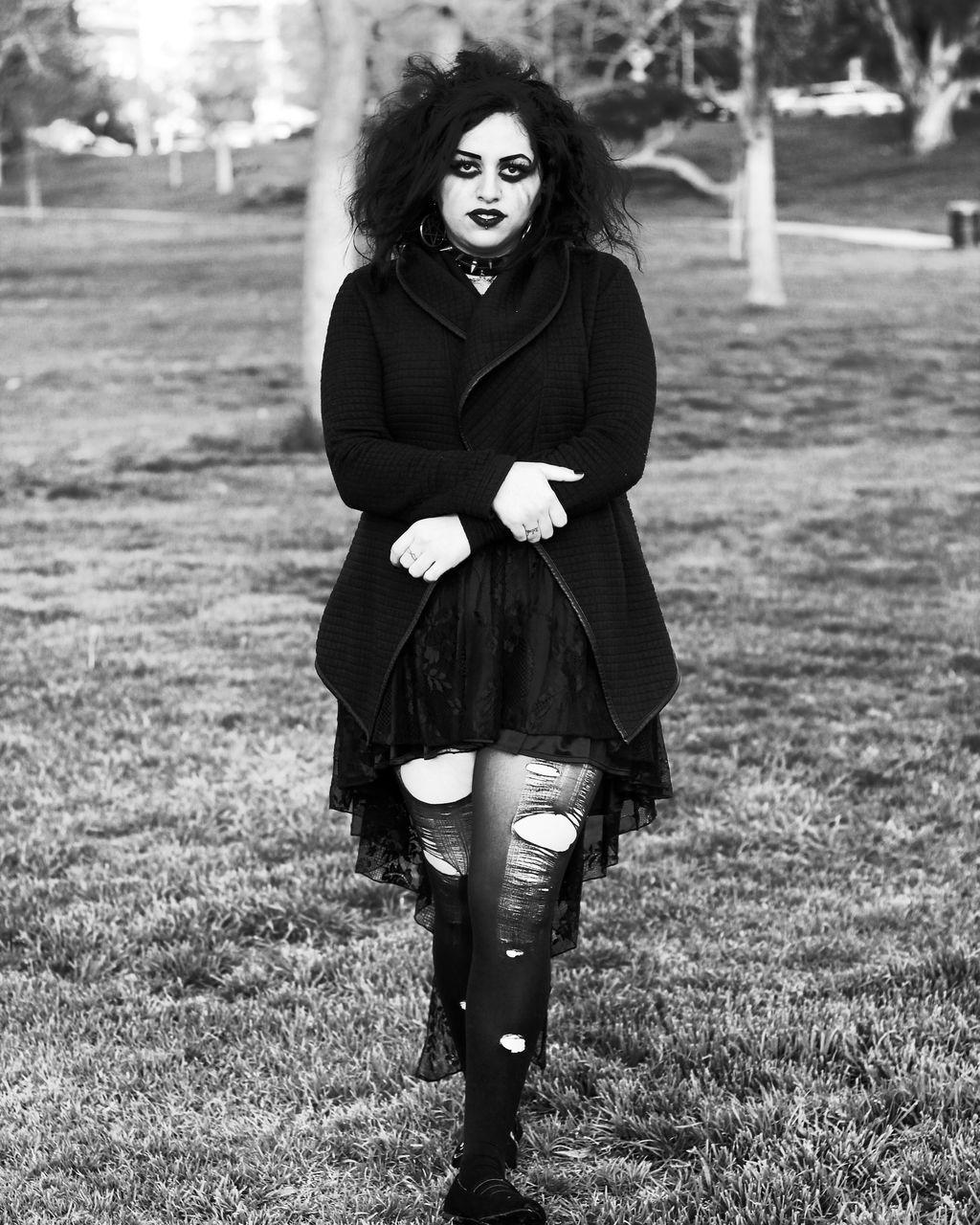 Portrait Of Gothic Woman Walking On Grassy Field