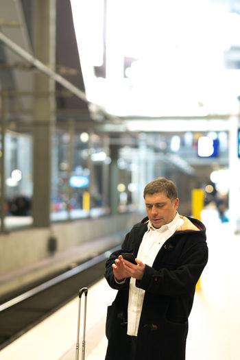 Man using mobile phone while standing at railroad station platform