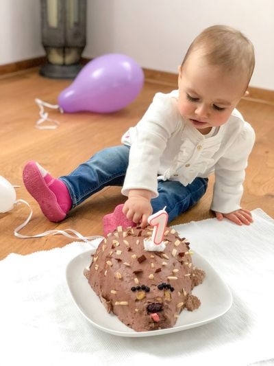 Cute Girl Touching Birthday Cake In Plate On Floor