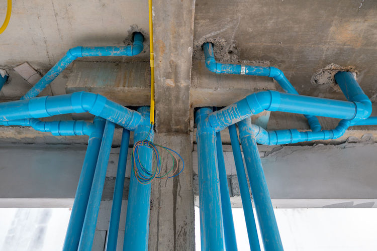 The tube water supply system in the building Blue No People Indoors  Metal Pipe - Tube Day Connection Yellow Industry Pipeline Wall - Building Feature Pipe Wood - Material Close-up Group Of Objects Architecture Technology Absence Water Pipe Turquoise Colored