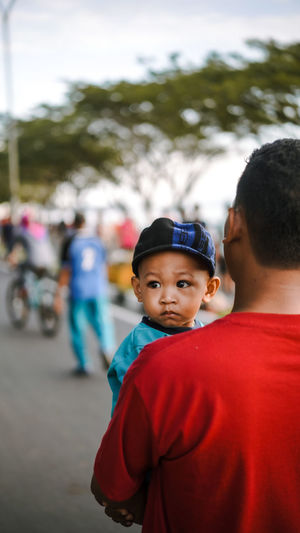 Rear view of man standing with baby boy on street
