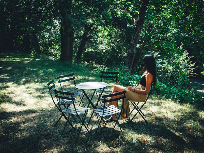 Woman sitting on chair at table in forest