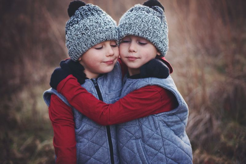 Twin brothers wearing knit hats embracing
