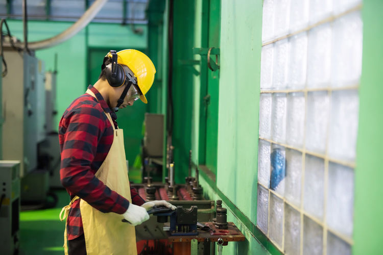 Skill mechanic worker working manual on lathe spare part metal in iron manufacturing factory.
