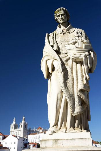 Sao Vicente Statue By Monastery Of Sao Vicente De Fora Church Against Clear Blue Sky