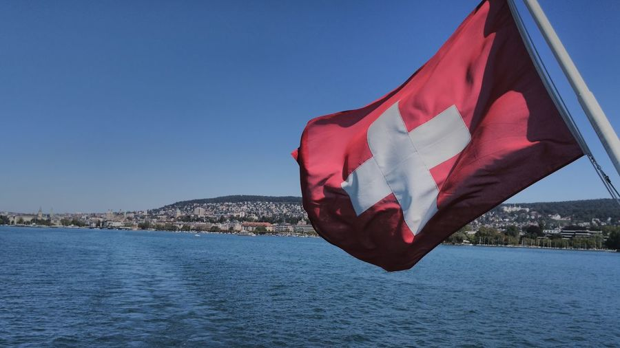 Swiss flag hanging over sea against sky