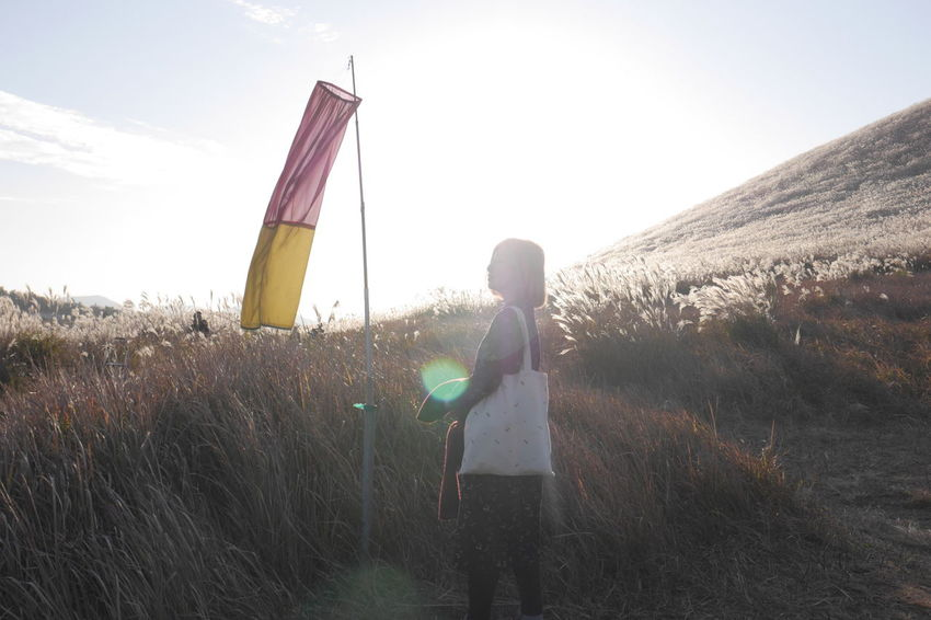 Casual Clothing Childhood Day Elementary Age Field Full Length Girls Grass Growth Leisure Activity Lifestyles Nature One Person Outdoors People Real People Rear View Sky Standing Sunset Sunshine