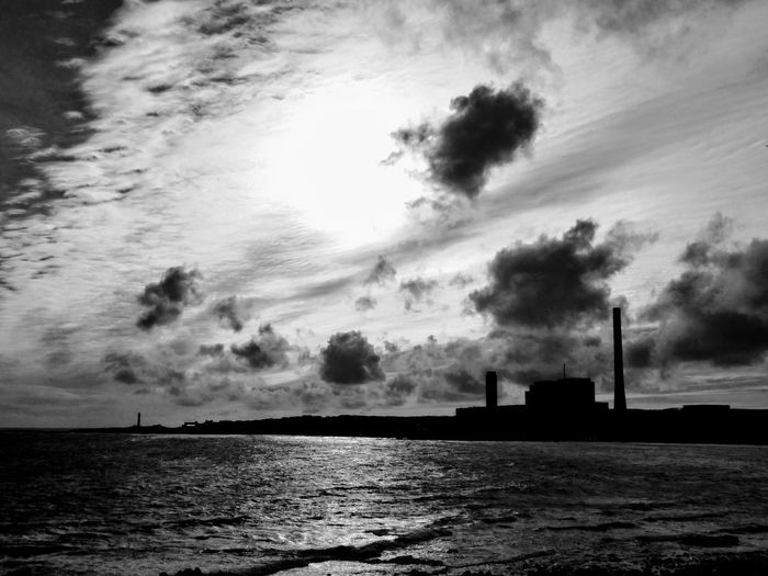 Silhouette factory by sea against sky