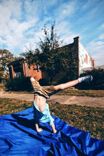Full length of boy performing handstand on blue fabric in yard
