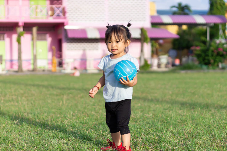Cute girl playing with ball on field