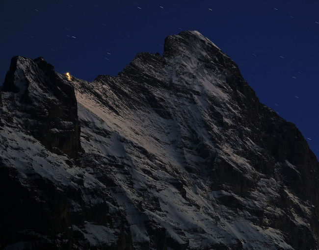 Low angle view of mountains against clear sky at night