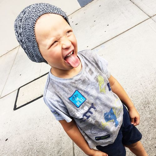 Tilt image of boy sticking out tongue on footpath