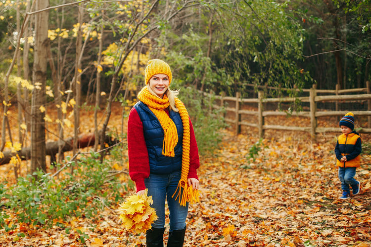 Smiling young woman standing in forest during autumn