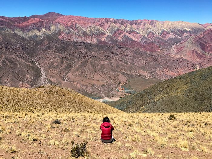 Woman sitting on landscape against sky