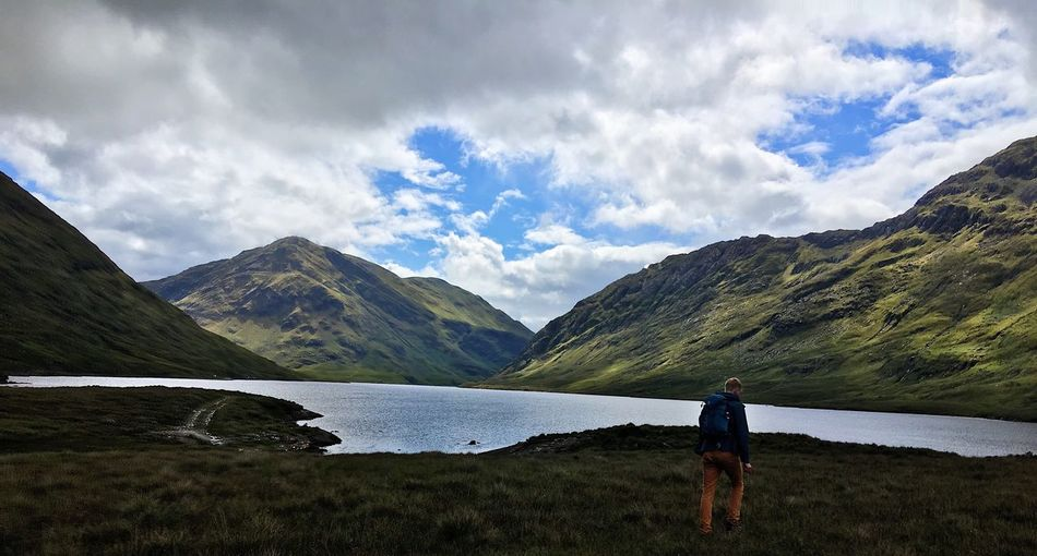 Rear view of man walking on mountain by lake against sky