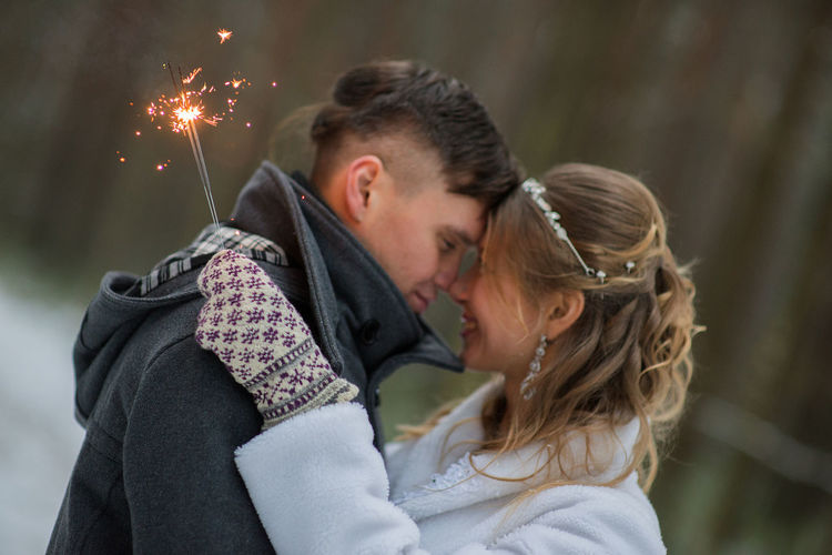 Happy couple with sparklers during winter