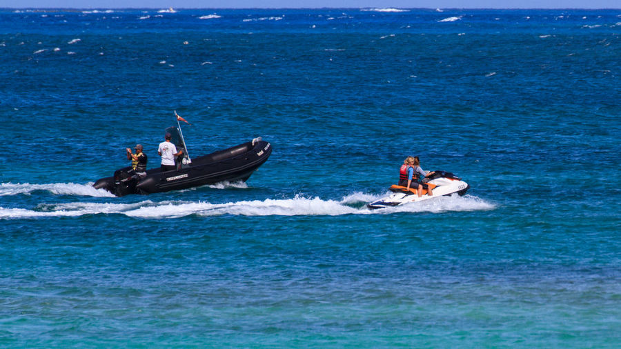 A motor boat and a couple jetskiing on the sea. Adult Adults Only Adventure Boat Day Jet Boat Jetboat Jetski Jetskiing Leisure Activity Lifestyles Men Motion Motorboat Nautical Vessel Outdoors People Sea Summer Transportation Wake - Water Water Water Bike Waterbike Waterfront