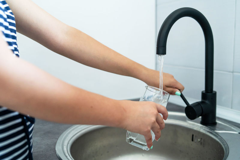 Midsection of woman filling drinking glass at sink