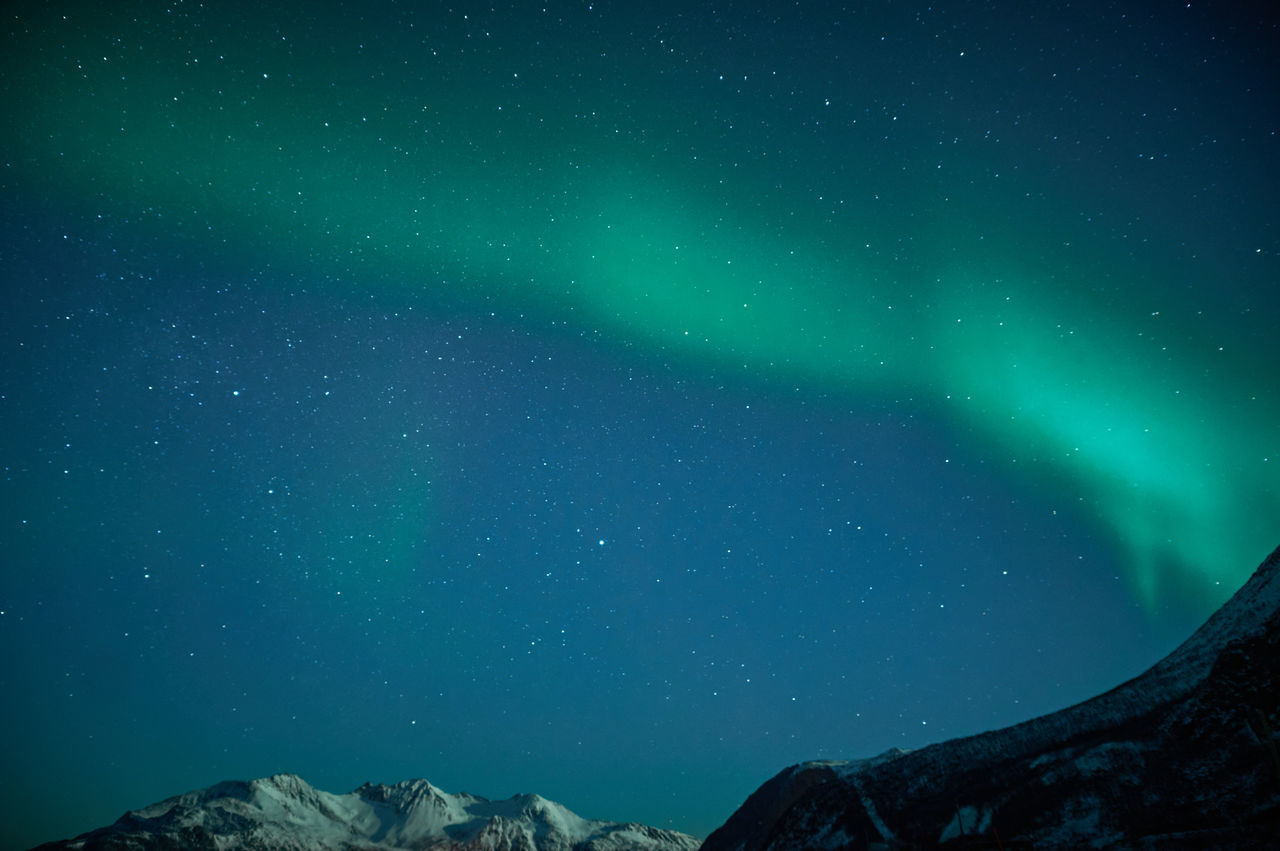 Low angle view of mountain and aurora borealis against sky at night