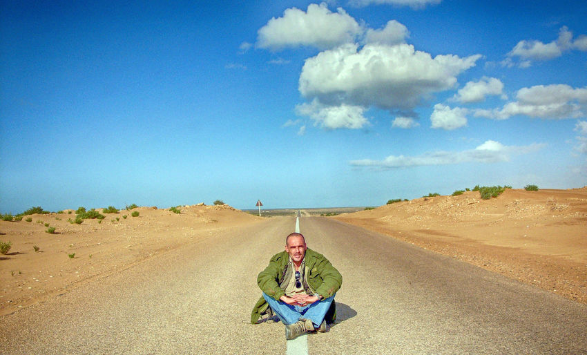 Sky Cloud - Sky Real People One Person Land Front View Sitting Nature Men Day Road Landscape Looking At Camera Leisure Activity Lifestyles Casual Clothing Environment Portrait Outdoors