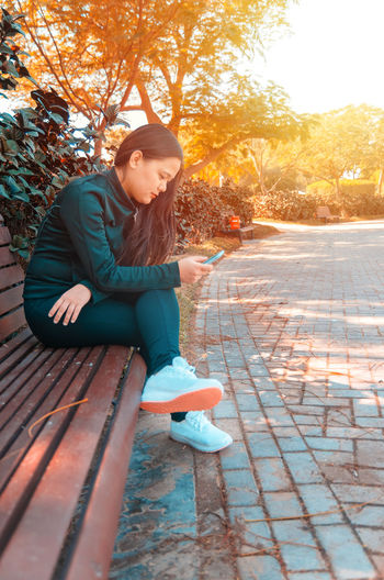 Side view of woman using phone on bench at park