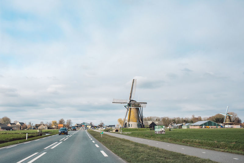 Traditional windmill on road against sky