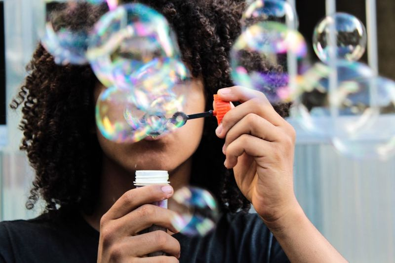 Close-up of young woman blowing bubbles